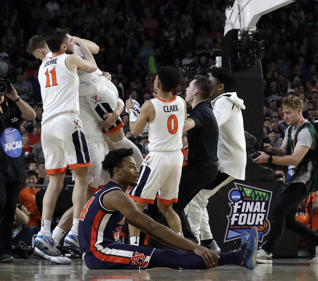 Auburn's Anfernee McLemore (24) reacts on the floor as Virginia celebrate after defeating Aubur ...