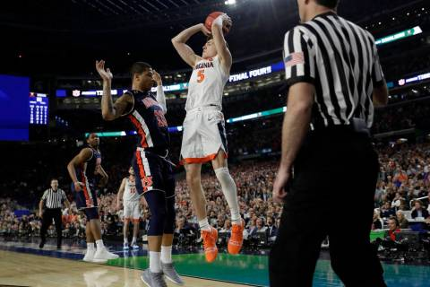 Virginia's Kyle Guy (5) takes a shot as Auburn's Samir Doughty (10) was called foul during the ...