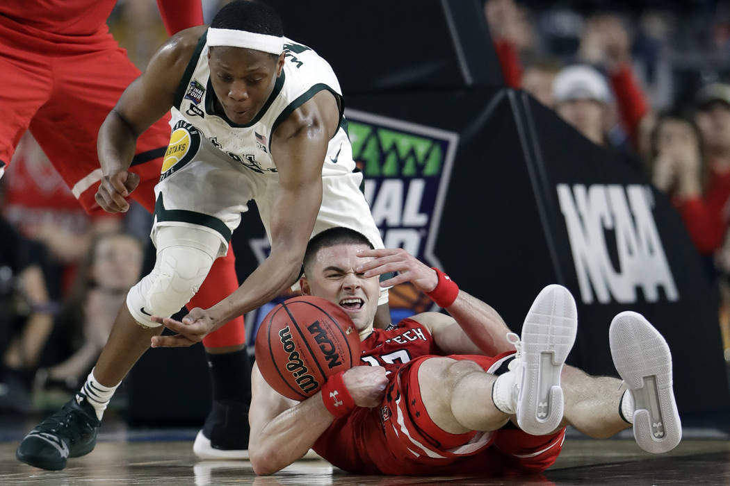 Texas Tech's Matt Mooney (13) battles for a loose ball against Michigan State's Cassius Winston ...