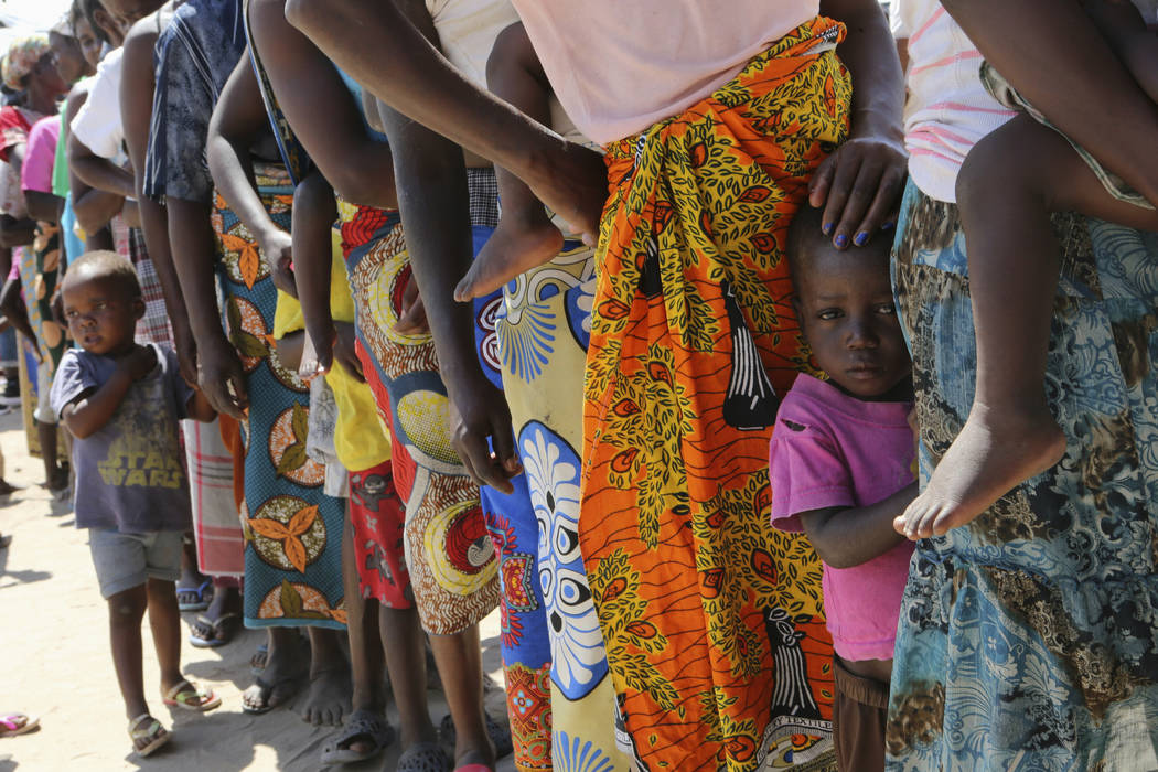 Women and children wait in a queue for oral cholera vaccinations, at a camp for displaced survi ...