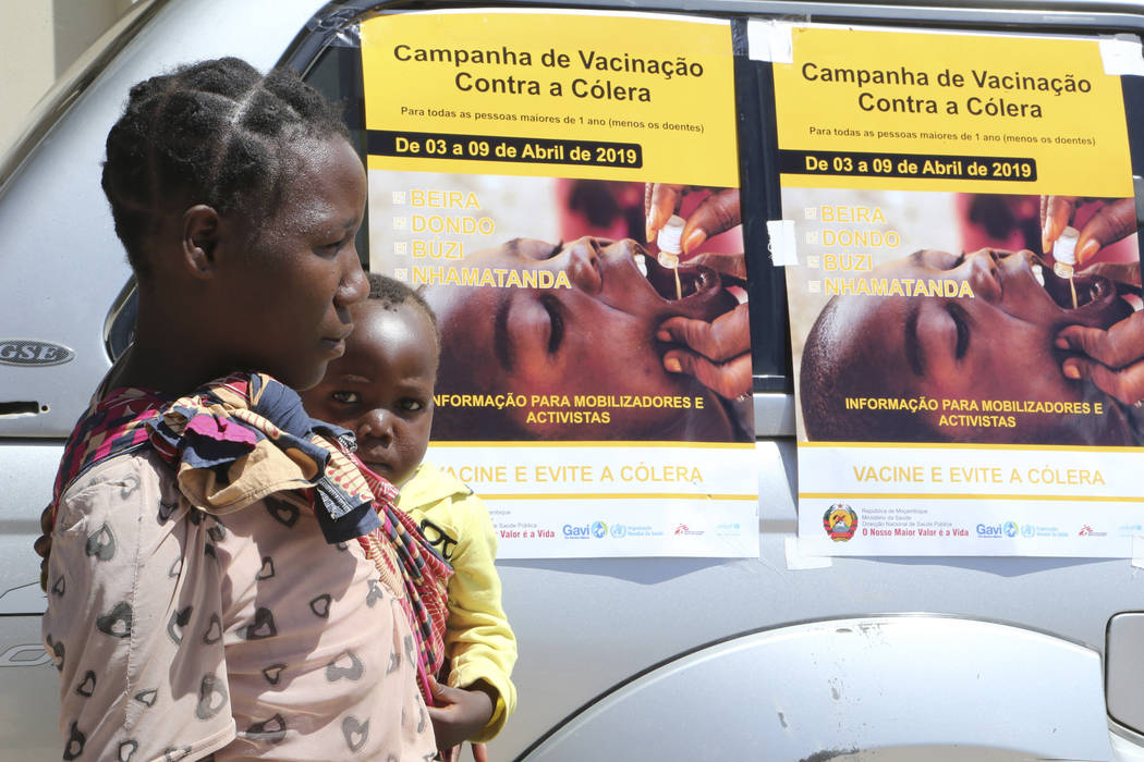 A woman and her baby walk past cholera vaccination campaign posters on the first day of the cho ...