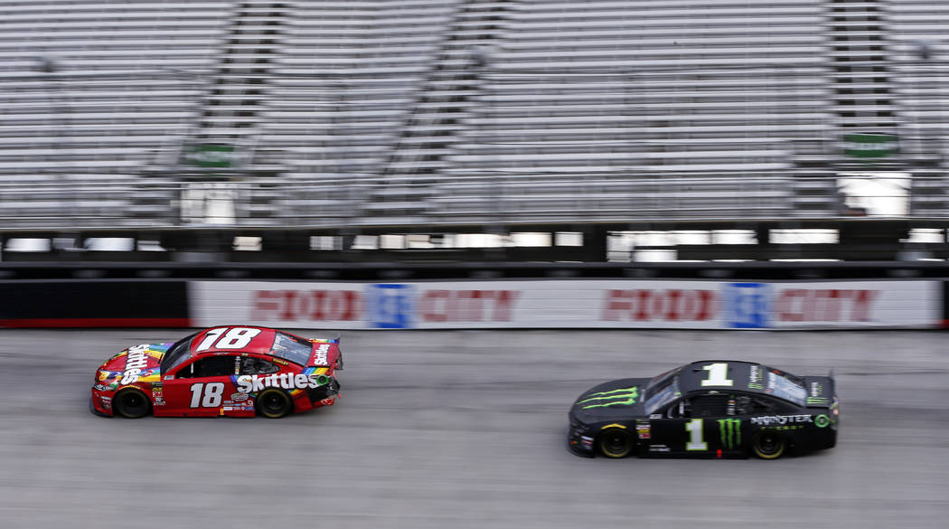 Kyle Busch (18) leads his brother Kurt Busch in the final laps of the NASCAR Cup Series auto ra ...