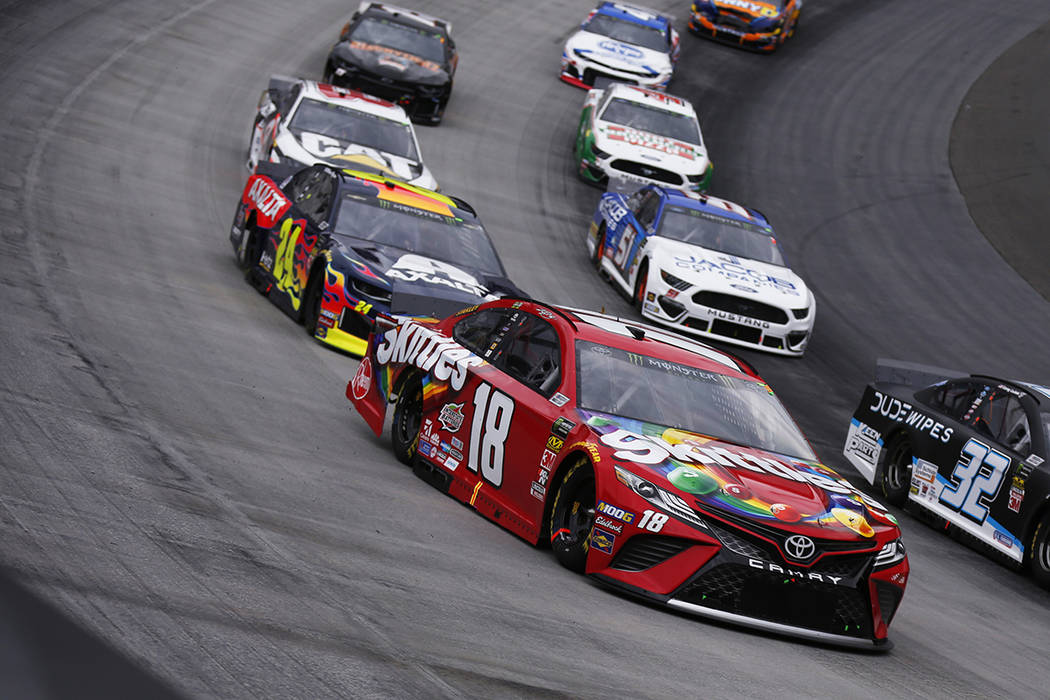 Kyle Busch (18) leads the fields through a turn during a NASCAR Cup Series auto race, Sunday, A ...
