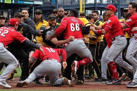 Cincinnati Reds' Yasiel Puig (66) pulls away from Tucker Barnhart (16) as he attempts to re-ent ...
