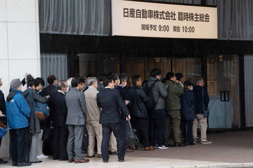In this photo released by Nissan Motor Co., Nissan shareholders wait to enter the venue for a m ...