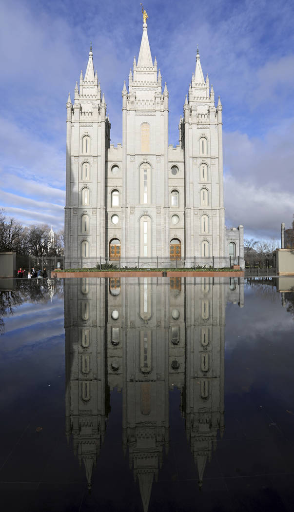 The Salt Lake City temple is reflected in a pool during The Church of Jesus Christ of Latter-da ...