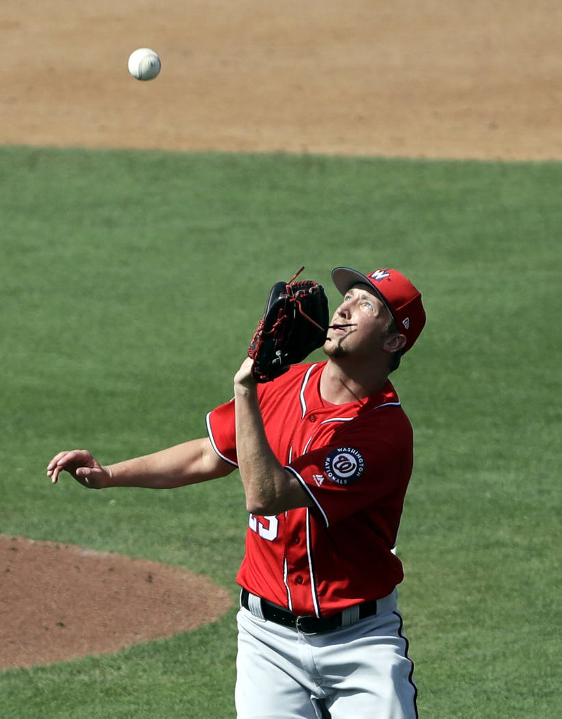 Washington Nationals pitcher Erick Fedde keeps his eye on a ball hit by Miami Marlins' JT Riddl ...