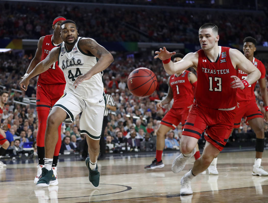 Texas Tech's Matt Mooney (13) chases a loose ball against Michigan State's Nick Ward (44) durin ...