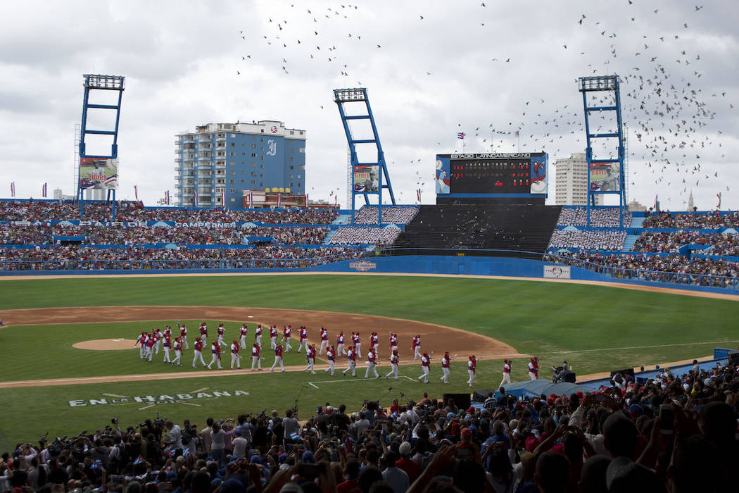 The Cuban national baseball team walks off the field as birds are released, at the start of the ...