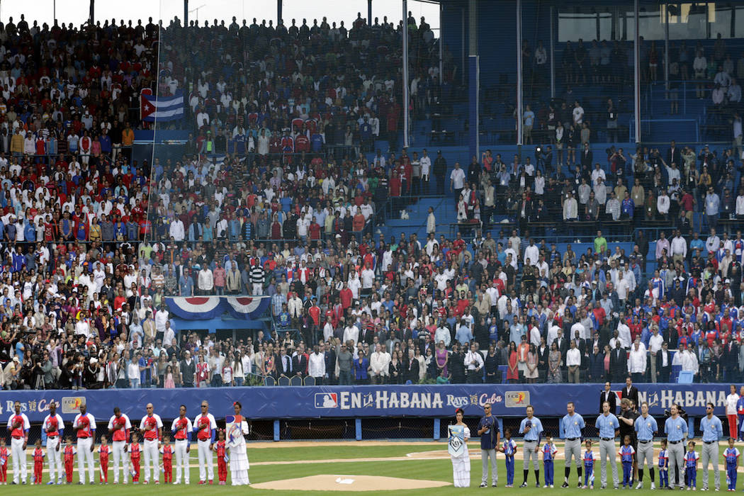 Tampa Bay Rays and the Cuban National team stand as the national anthems are played before thei ...