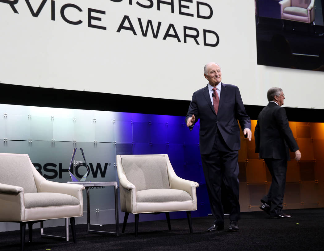 Actor, director, screenwriter and podcaster Alan Alda, left, walks on stage to receive the Dist ...