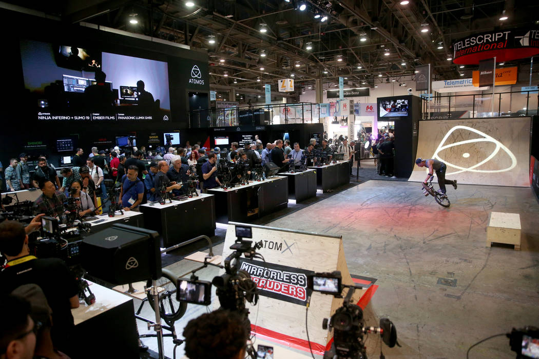 A professional BMX rider does tricks so conventioneers can check out camera monitors at the Ato ...