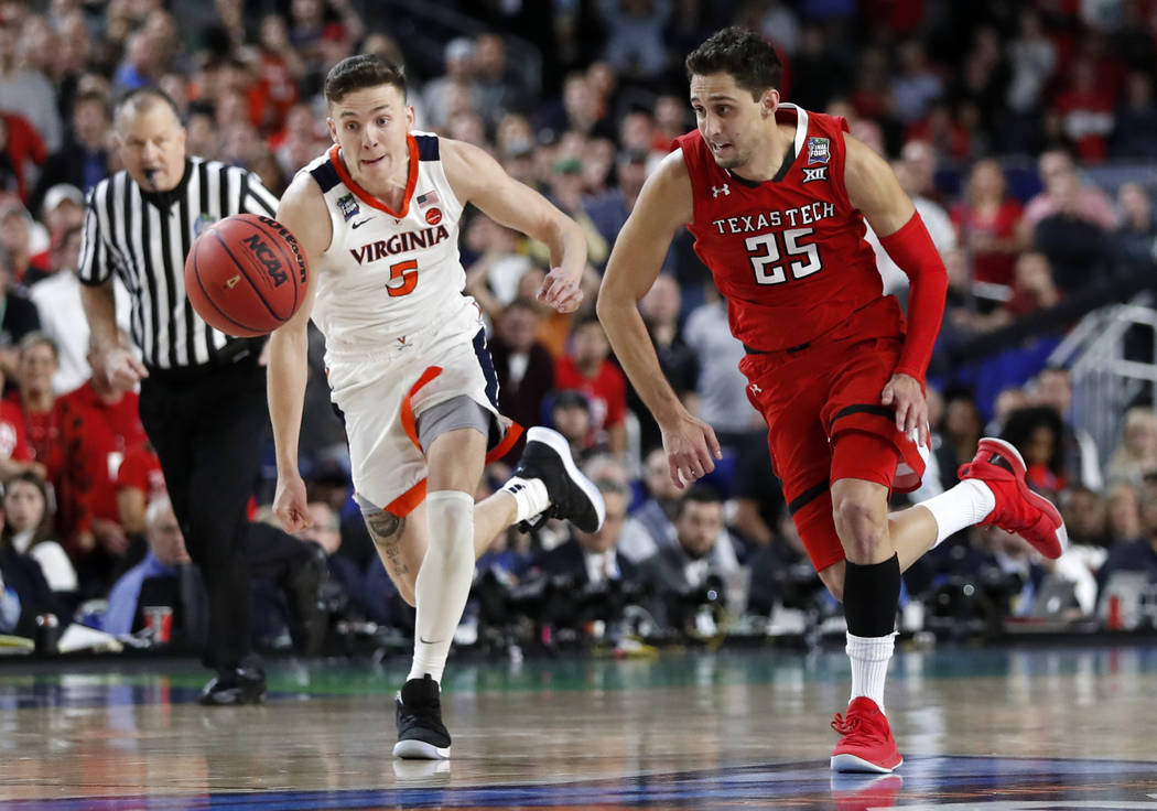 Virginia's Kyle Guy (5) and Texas Tech's Davide Moretti (25) chase a loose ball during the over ...