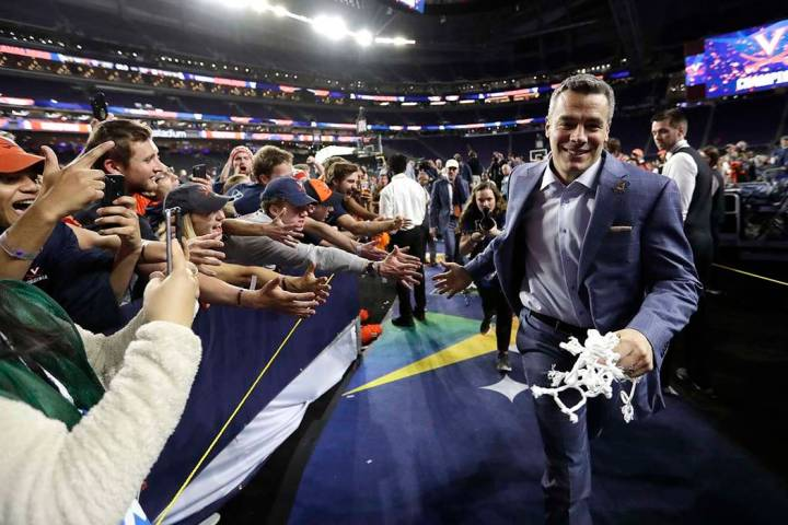 Virginia head coach Tony Bennett celebrates with fans after the championship game against Texas ...