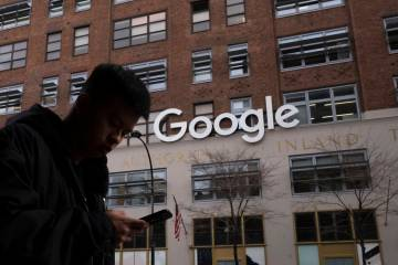 A man using a mobile phone walks past Google offices in New York on Dec. 17,2018. Executives fr ...