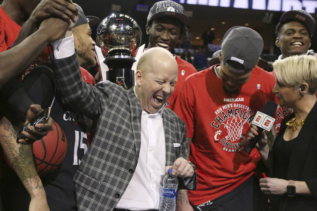 In this March 17, 2019, file photo, Cincinnati coach Mick Cronin high-fives one of his players ...