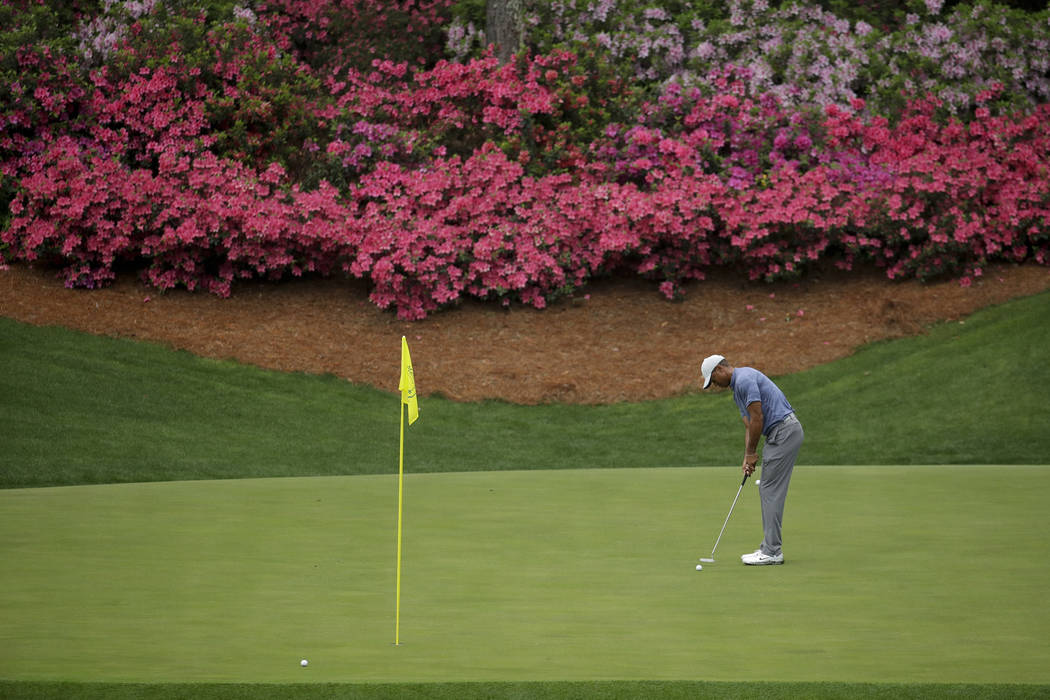 Tiger Woods putts on the 13th hole during a practice round for the Masters golf tournament Mond ...
