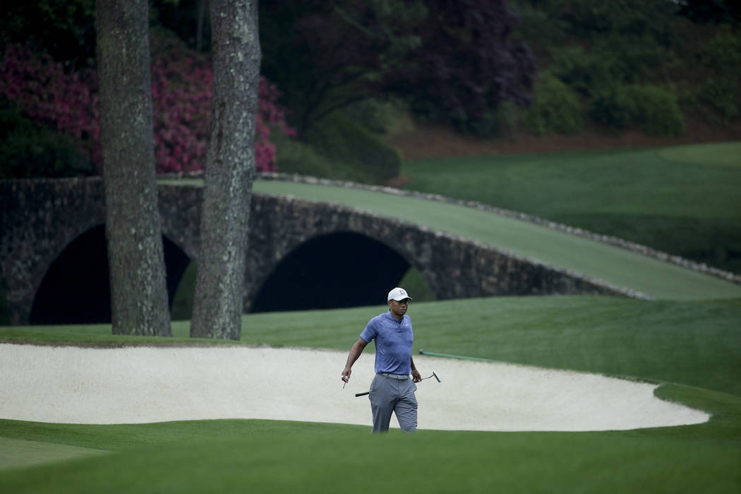 Tiger Woods walks off the 11th green during a practice round for the Masters golf tournament Mo ...
