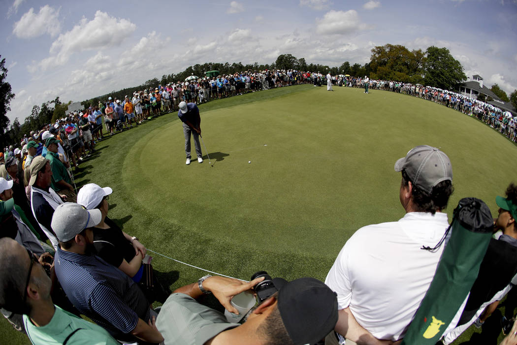 Tiger Woods putts on the practice green after a practice round for the Masters golf tournament ...