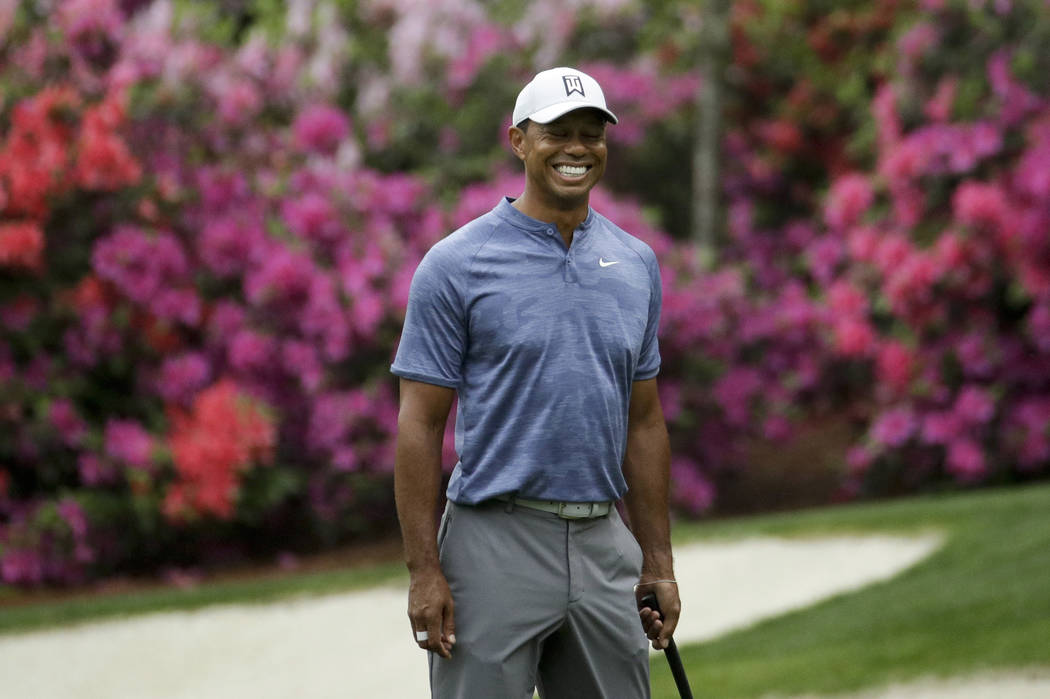 Tiger Woods smiles as he walks off the 13th green during a practice round for the Masters golf ...