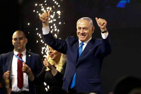 Israel's Prime Minister Benjamin Netanyahu waves to his supporters after polls for Israel's gen ...