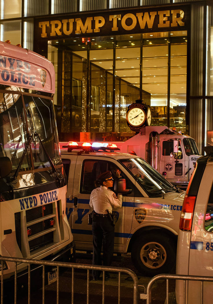 Police stand guard and trucks are parked in front of Trump Tower as a security measure against ...