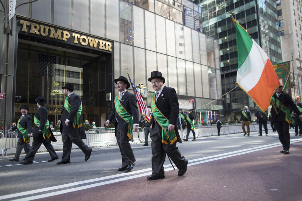 Participants march up Fifth Avenue past Trump tower during the St. Patrick's Day Parade, Saturd ...
