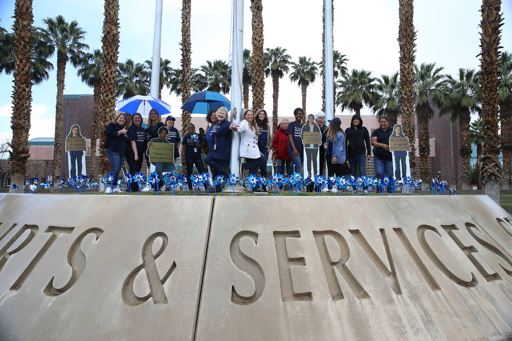 Volunteers are photographed after planting 450 pinwheels outside of the Eighth Judicial Distric ...