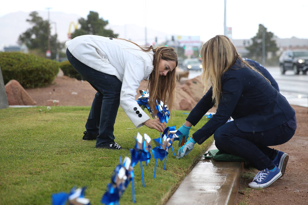 Volunteers Rochelle Vannoy, left, and Heather McCusker, plant pinwheels outside of the Eighth J ...