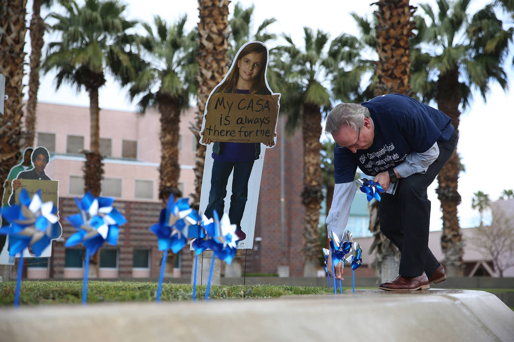 District Judge Bryce Duckworth plants pinwheels outside of the Eighth Judicial District Family ...