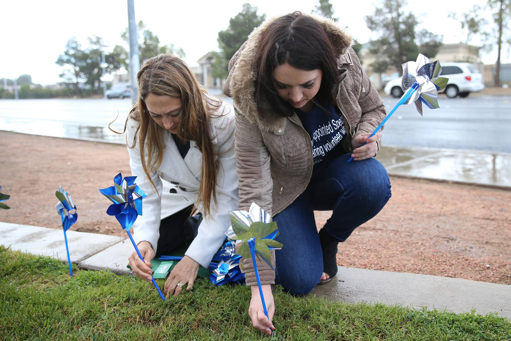 Volunteers Rochelle Vannoy, left, and Lisa Coruzzi, plant pinwheels outside of the Eighth Judic ...