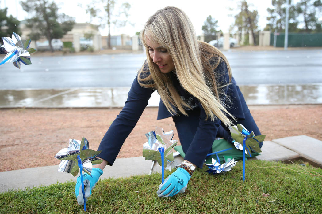 Volunteer Heather McCusker plants pinwheels outside of the Eighth Judicial District Family Cour ...