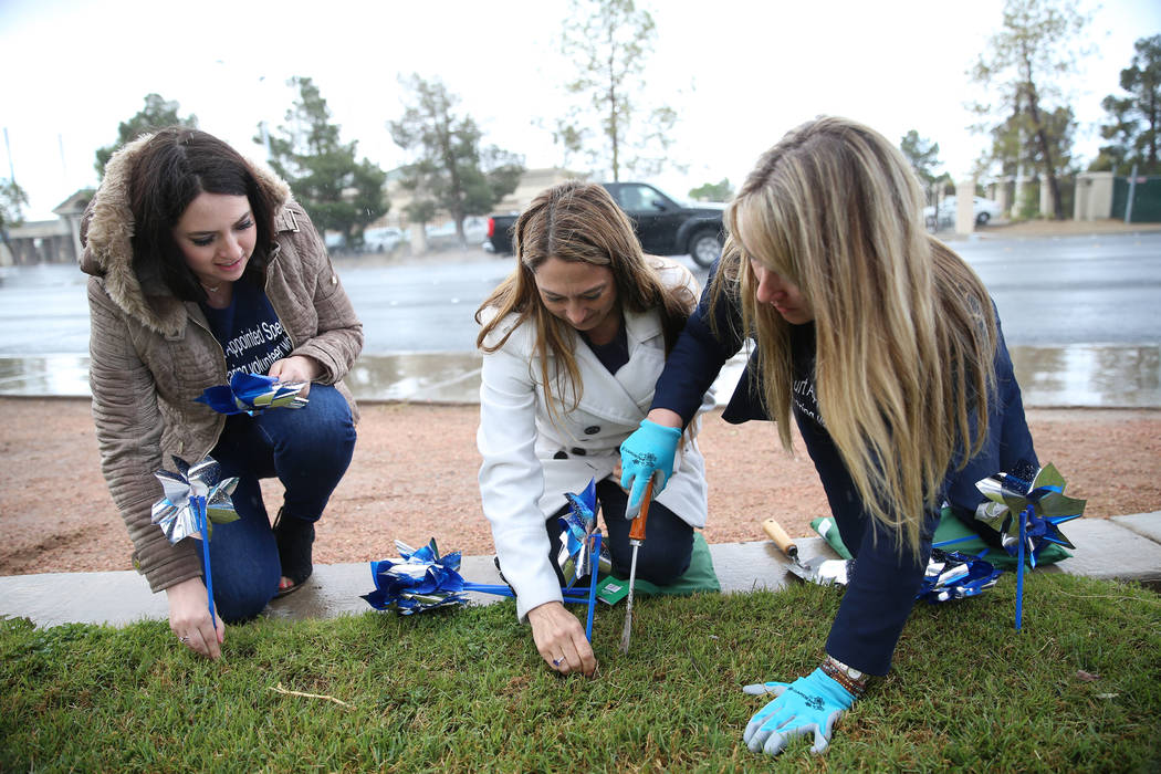 Volunteers from left, Lisa Coruzzi, Rochelle Vannoy, and Heather McCusker, plant pinwheels outs ...