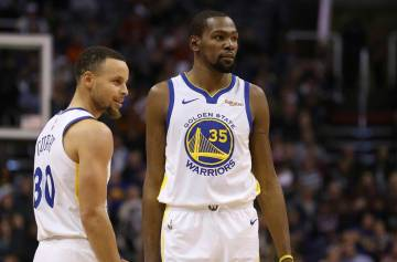 Golden State Warriors guard Stephen Curry (30) and forward Kevin Durant (35) pause during the f ...