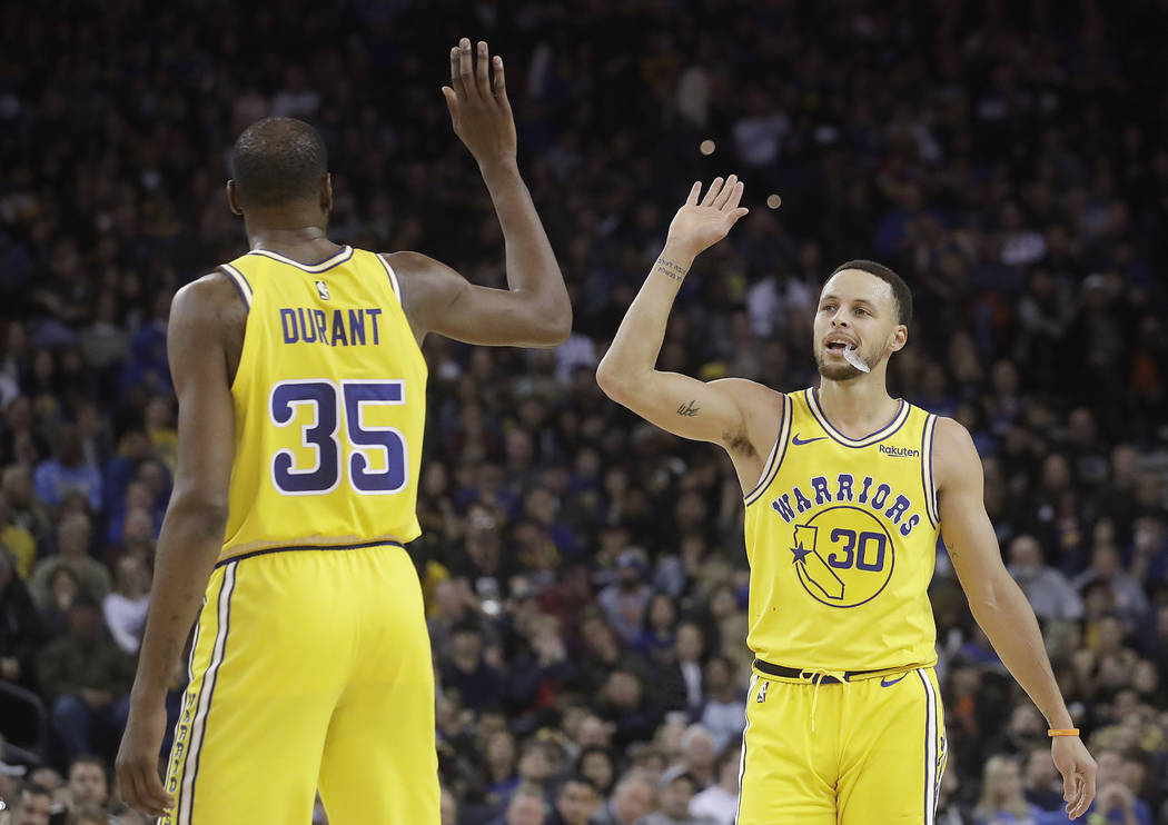 Golden State Warriors forward Kevin Durant (35) celebrates with guard Stephen Curry (30) during ...