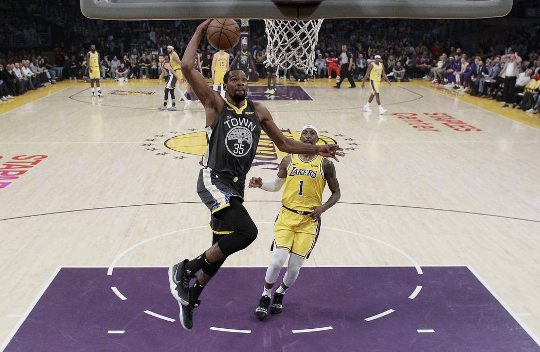 Golden State Warriors' Kevin Durant (35) dunks past Los Angeles Lakers' Kentavious Caldwell-Pop ...