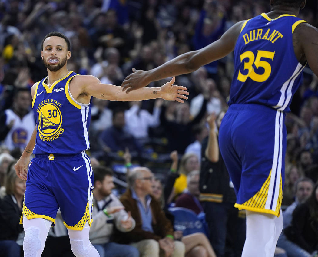 Golden State Warriors' Kevin Durant (35) high-fives Stephen Curry (30) after Curry made a 3-poi ...
