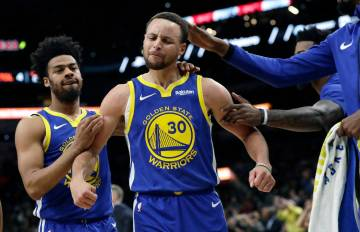 Golden State Warriors guard Stephen Curry (30) is grabbed by teammates as he reacts after being ...