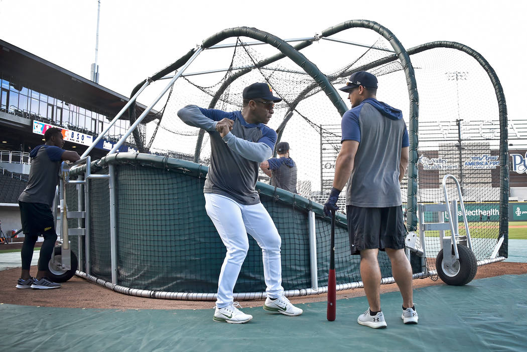 Retired Major League baseball player and now special coach Rickey Henderson, center, works with ...