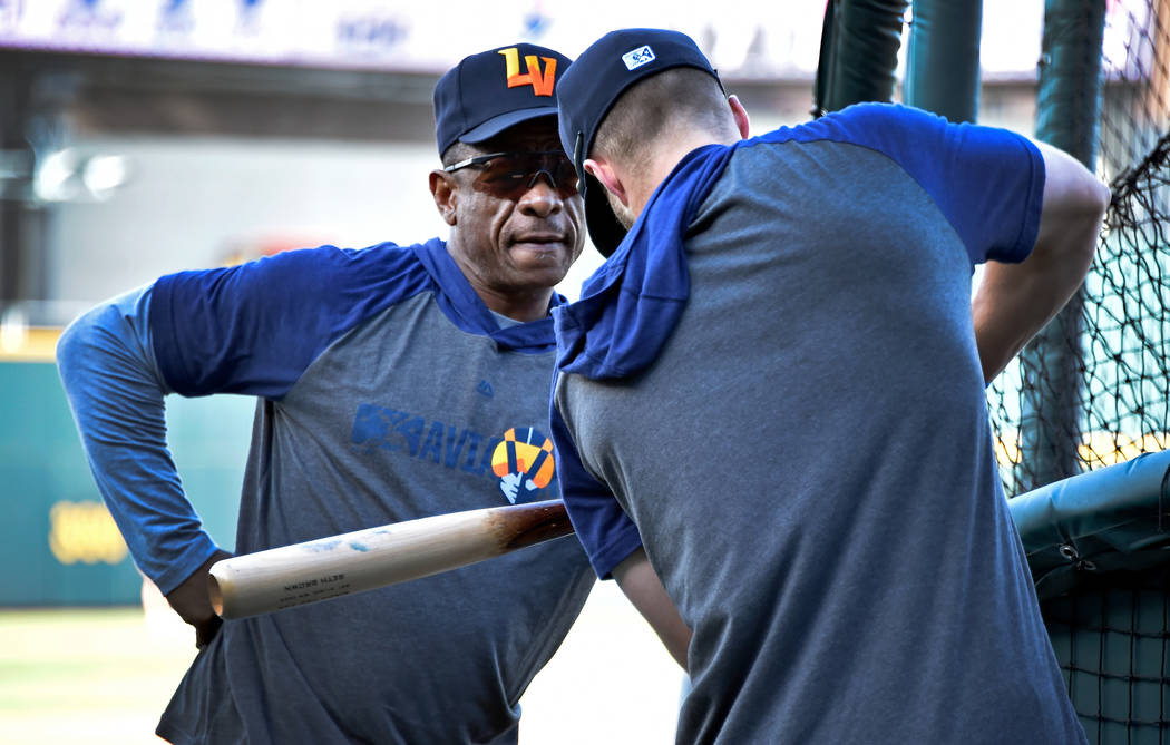 Retired Major League baseball player and now special coach Rickey Henderson, left, works with L ...