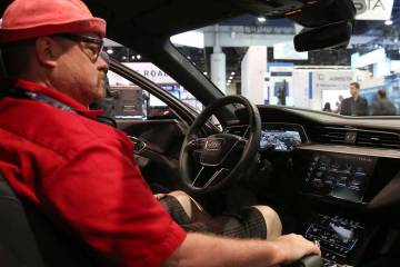 Kory Mortensen checks out digital dashboard display inside Audi e-tron during the National Asso ...