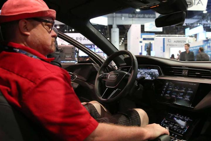 Kory Mortensen checks out digital dashboard display inside Audi e-tron during the National Asso ...