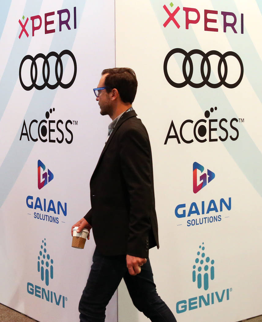 Showgoer walks past In-Vehicle-Experience booth during the National Association of Broadcasters ...