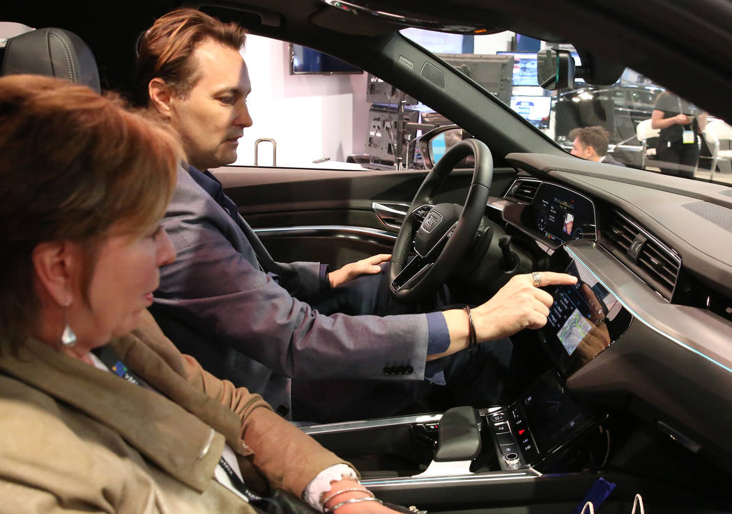 Showgoers check out digital dashboard display inside Audi e-tron during the National Associatio ...