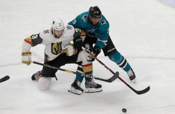 San Jose Sharks left wing Evander Kane, right, reaches for the puck next to Vegas Golden Knight ...
