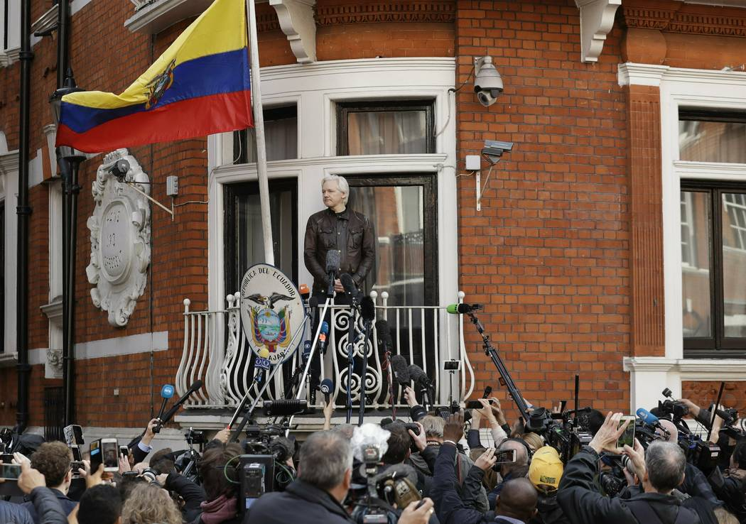 Watched by the media WikiLeaks founder Julian Assange looks out from the balcony of the Ecuador ...