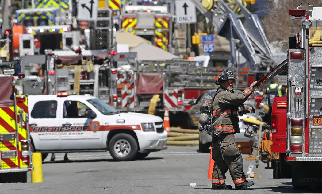 Firefighters and emergency personnel work the scene of an explosion and building fire in downto ...