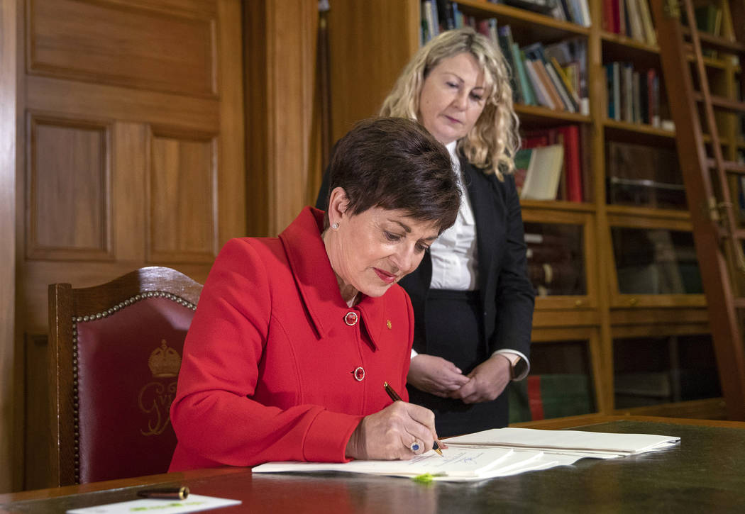 New Zealand Governor General Patsy Reddy, left, assisted by the Deputy Clerk of the House, Suze ...