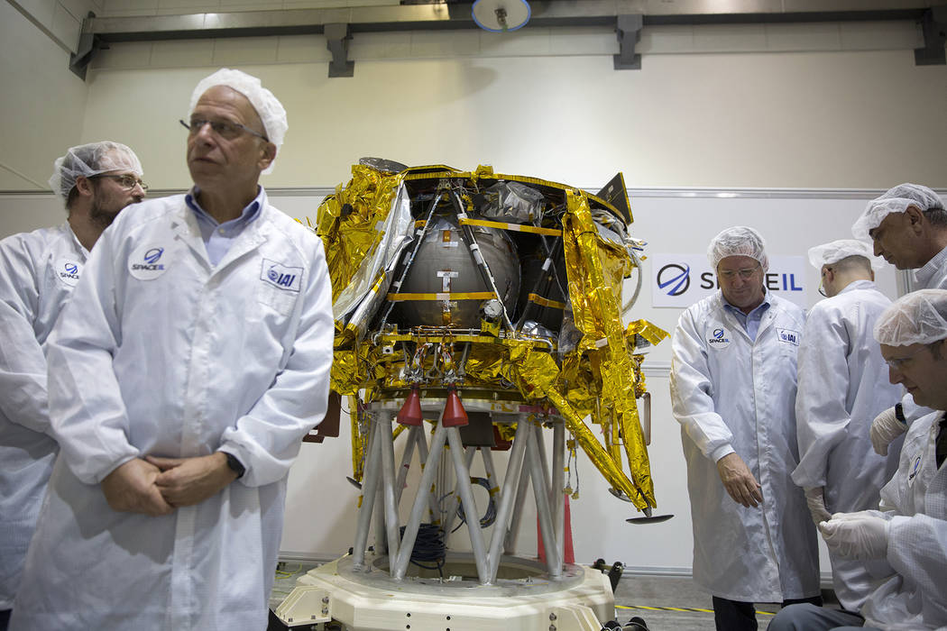In this Monday, Dec. 17, 2018 file photo, technicians stand next to the SpaceIL lunar module, a ...