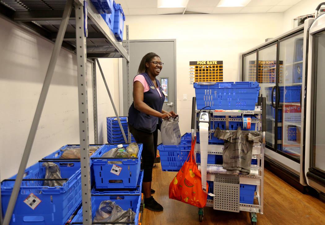 Walmart Associate Kiara D. preps carts for online pickup orders in the online grocery pickup ro ...